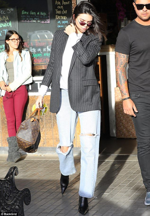 Eclectic: Kendall layered a grey sweater under a pinstripe suit jacket