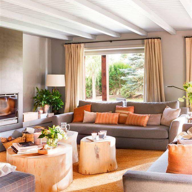 Salón gris, blanco y marrón con mesa de centro tronco, chimenea, cojines rojizos y plantas