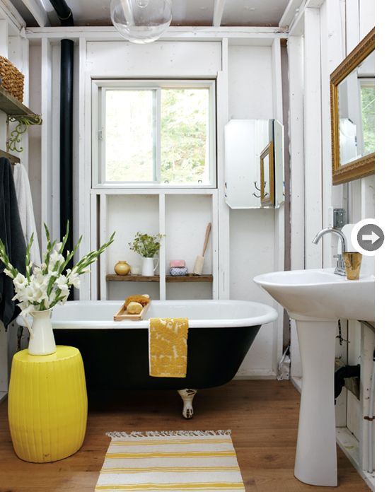 Layering rustic elements like reclaimed-wood shelving with a sophisticated gold, charcoal grey and white scheme creates a rich depth in the bathroom. A fun find like this claw-foot tub was bought for $120 from a nearby farmer. A quick coat of charcoal paint was then used to make it pop beautifully against the white