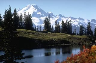 Glacier-covered Mount Baker, the centerpiece of the Mount Baker Wilderness Area, is seen here from Twin Lakes on the north. Sherman Crater, the source of historical eruptions from Mount Baker, appears from this perspective on the left side between the summit and the small sharp-topped Sherman Peak. The older dissected Black Buttes volcano forms the two sharp peaks below and to the right of the summit.