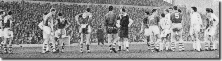 12th October 1963. The referee calls together players from Leeds and Huddersfield Town following an avalanche of toilet rolls thrown by supporters at Leeds Road.