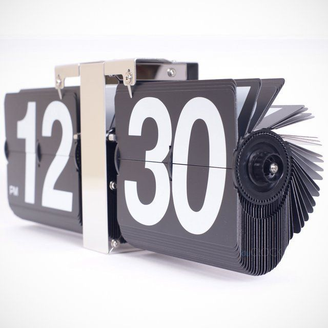 """This is the wall clock that displays the time on giant, easy-to-read panels that flip the minutes away. Inspired by the classic flip clocks of yesteryear, this version uses bold 3 1/2"""" tall white numbers printed on black 3 3/4"""" x 5"""" vinyl split panels. Morning and evening hours are distinguished with an AM or PM printed on the hour panel. Each passing minute is accompanied by a pleasant, ambient clattering that underscores the analog flip clock's mechanical operation..."""