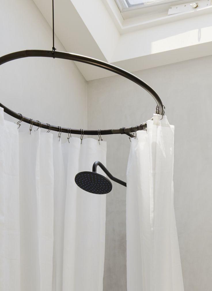 bronze circular shower ring in white plaster finish bathroom