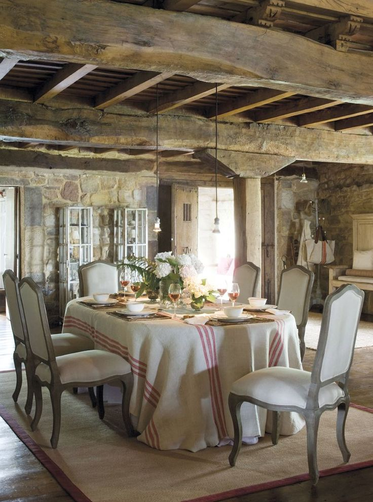 French Provençal Chairs in old stone dining room with wood beams.