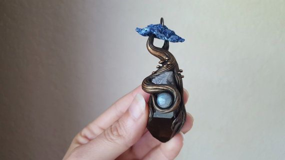 This handmade pendant is created from natural objects and a durable waterproof clay. A Large smokey quartz tip creates the base of the pendant. A majestic, hand sculpted canopy tree with bonsai like twists, has roots clutching the large crystal and flashy labradorite cabochon. It is hand painted with acrylic paint and sealed with a water resistant sealant.   Each tree will come in a wooden box(wish hand painted lid), laid in a bed of moss. See photos for size reference. Contact me directly…