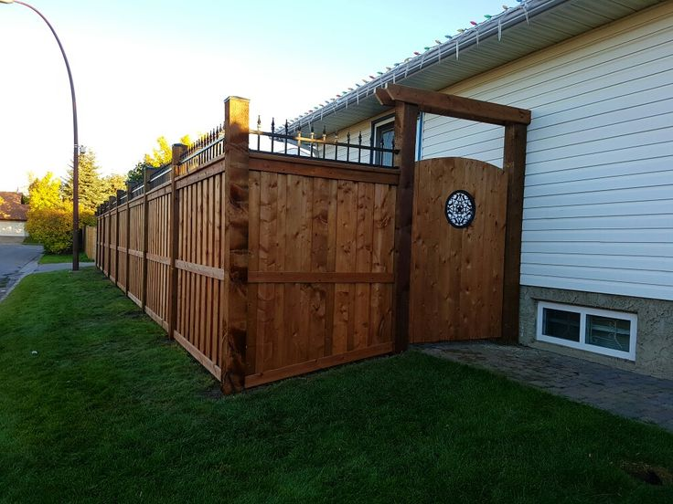 Fortress Style fence with simple gate and insert with a  arbour over head