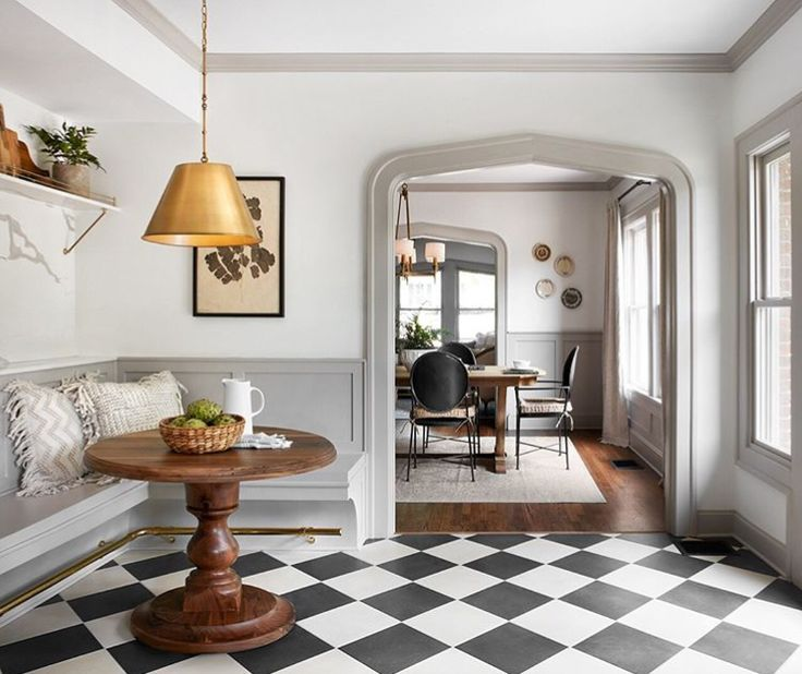 Gorgeous breakfast nook in a kitchen with European inspired design, black and white check floors, light grey trim, white walls, modern lighting, and romantic timeless style. #homedecor #vintagestyle #fixerupper