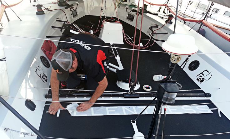 Side Effects Graphics installs deck gripping and lettering to a sail boat deck.