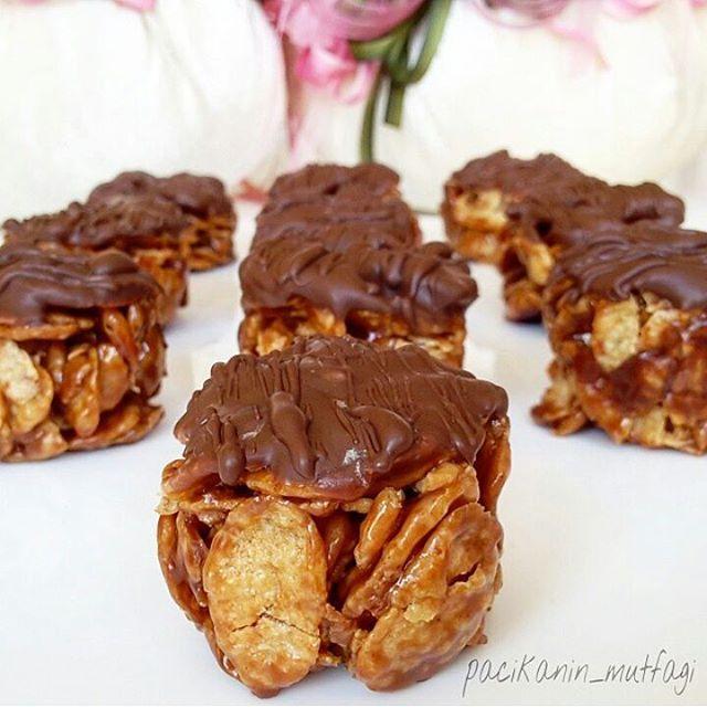 Metrolu mısır gevrekli kurabiye 4 adet metro çikolata 2 yemek kaşığı tereyağı 1 yemek kaşığı bal 150-200 gr kadar sade mısır gevreği İsteğe göre fındık fıstık ceviz Üzeri için eritilmiş çikolata Yapılışı: Öncelikle metroları küçük küçük doğrayıp yapışmaz bir tencereye ya da tavaya alalım ve tereyağıyla beraber eritelim. Sonra gevrekleri ve balı ekleyip bir iki dakika daha kar