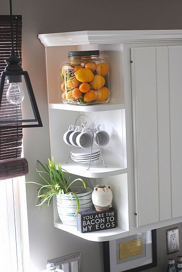 Open shelves on the end of the kitchen cabinets add visual interest, color, and storage space!