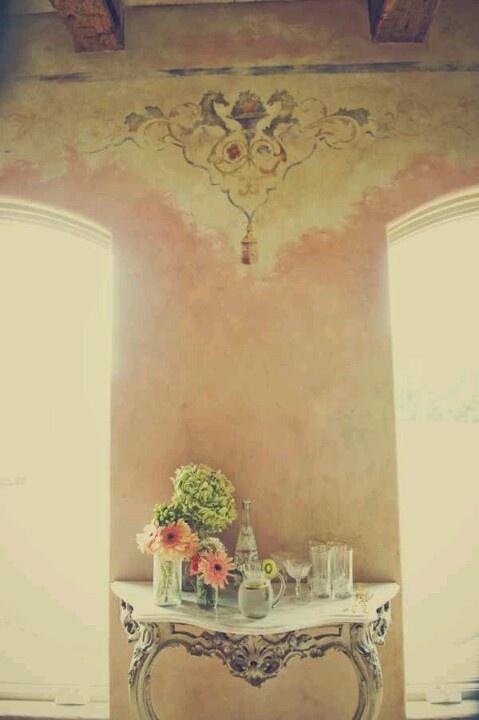 Antiek tafeltje, antieke spiegel en grote vaas met bloemen of plant.