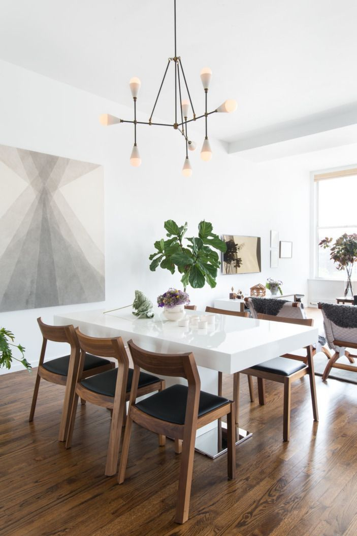 In keeping with the sleek, white lines of the apartment, the dining table is a simple, white lacquered piece, surrounded by walnut chairs to warm up the look.