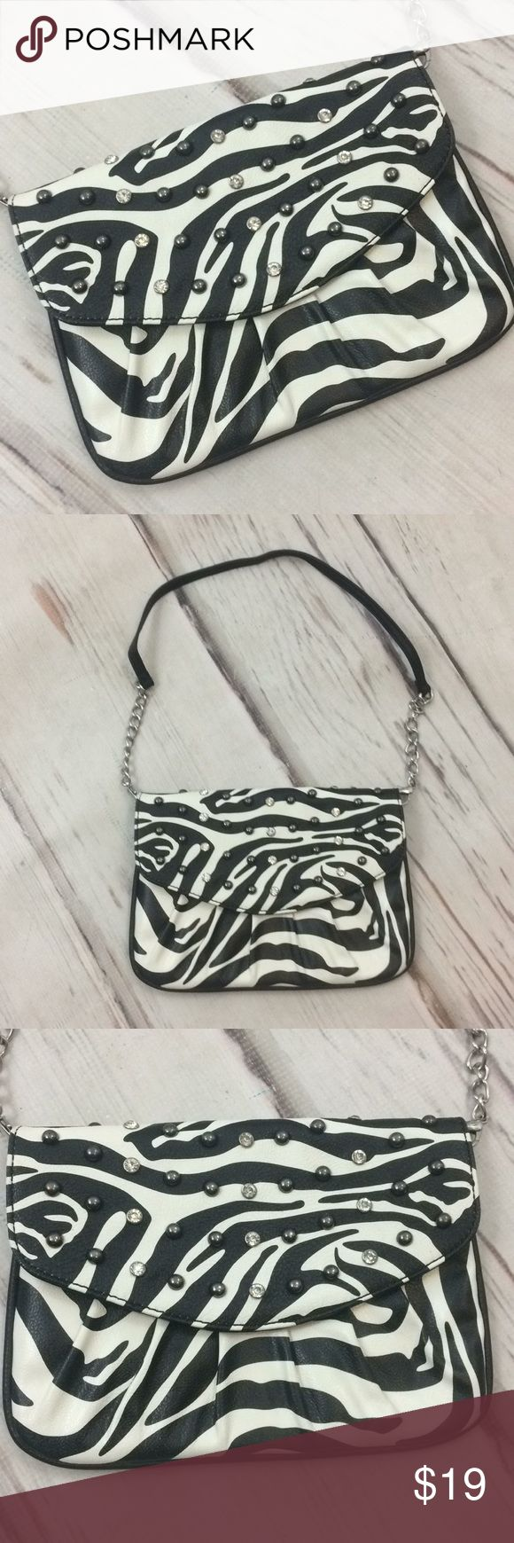 """Grace Adele zebra print rhinestone studded purse Grace Adele small purse chain strap white zebra metallic stud  Small purse with removable shoulder strap of faux leather and chain link. Snap front . Zipping pocket and three card holder slots. One cell phone pocket. Very minor signs of wear or use. Brand is Grace Adele.  9"""" wide. Height 6.75"""". .5"""" thick at bottom 1"""" at top with flap. Strap 25"""". Grace Adele Bags Shoulder Bags"""