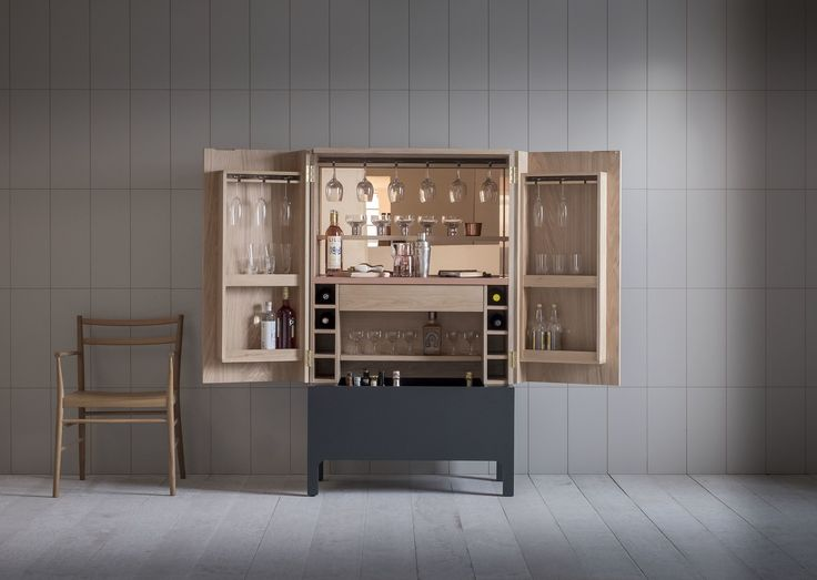 A drinks cabinet with timber and lacquered exterior and cast copper handles. Interior features peach tone mirror, warm LED lighting, a satin copper lacquered work surface, adjustable shelves to allow for bottle and glass height, stained and silicon-lined drinks trough, wine storage, and dovetailed storage drawer and glass stem hanging boxes.