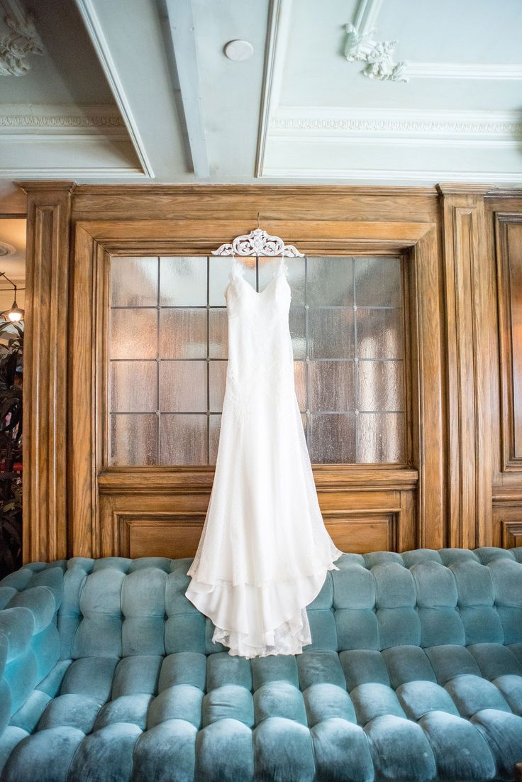 Mikkel Paige Photography captures a luxury wedding in NYC. The bride's David Fielden wedding gown hangs in the lobby of The Marlton Hotel.