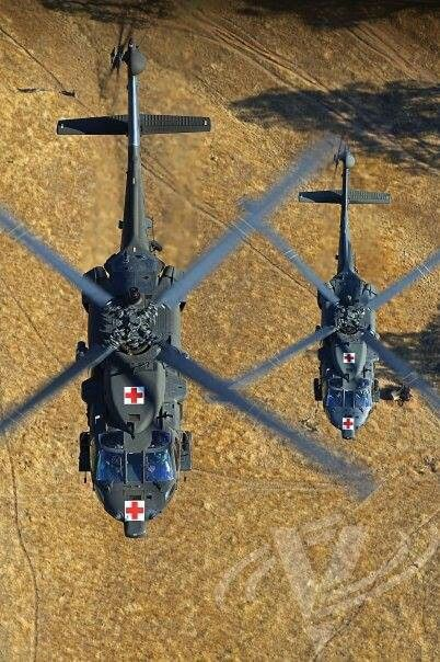 A pair of UH-60 medical Blackhawks flying in formation.