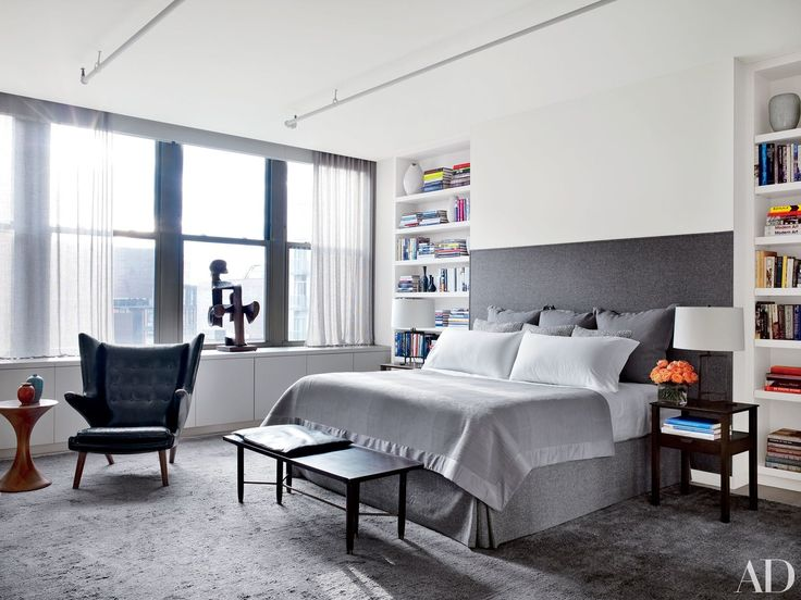 The master bedroom is anchored by a bed with a custom-made headboard.