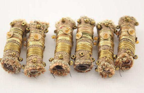 Fibra textil arte de cuentas con base de tuberías de plomería. Envuelto en 2 tonos de seda y embeliished con hilo verde oliva oscuro, oro e hilo de algodón variopinto una pizca de granos de la semilla, un toque de hilo metálico dorado y lentejuelas hace que estos granos brillan y brillan como joyas de la corona! Cada cuenta es único y recibirá los 6 granos que se muestra en las imágenes. Son aproximadamente 1.1/2(4cm) de longitud. Tienen amplia suficiente apertura para coser y tendido y muy…