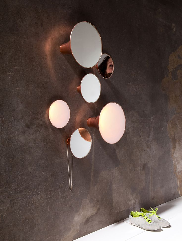"""*Sirens is amirror and light object, that attracts attention but in a silent and poetic way. The elegant silhouette is combined with shiny copper and extends into the living space bringing the mirrors and the ambient light aesthetically to the front. """"Sirens"""" are hand-crafted of copper with an old spinning technique."""