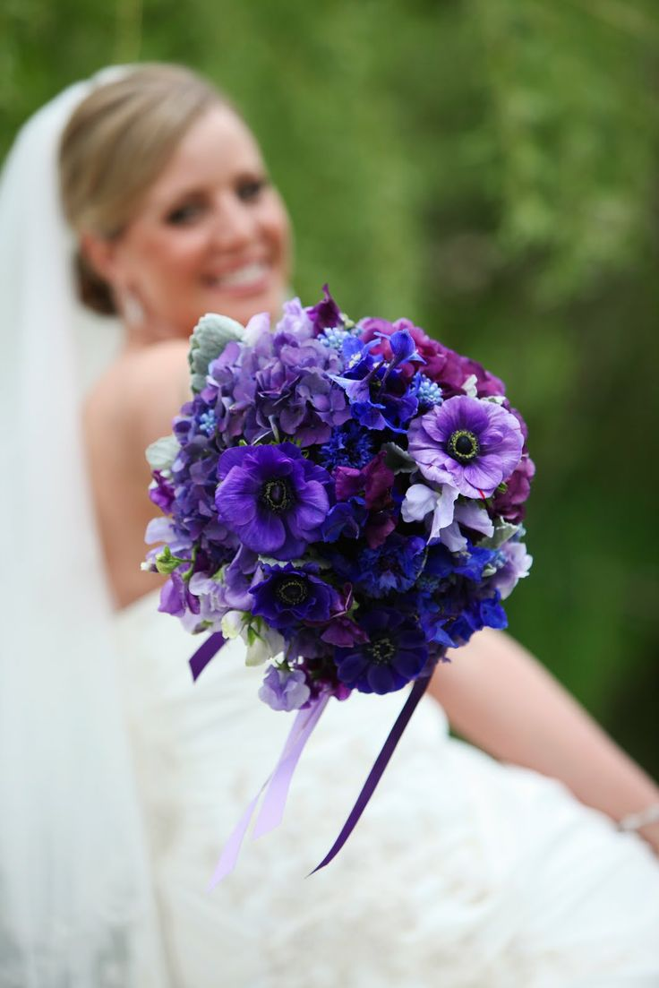 Purple and blue bouquet consisting of all purples anemones, hydrangeas, sweetpeas with blue muscari, delphinium, bachelor buttons and accents of dusty miller leaves