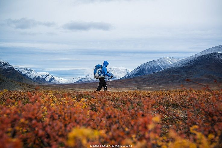 Female hiker with snow covered mountains and autumn colors in southern end of Tjäktjavagge on Kungsleden trail, Lappland, Sweden