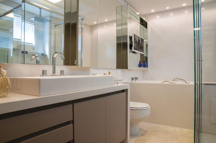 Os cristais também aparecem no banheiro, aplicados nos azulejos que revestem as paredes. O armário com portas em espelho estende-se até a área da banheira, onde dá lugar a um painel espelhado de suporte à TV. Bancada em silestone branco envolve o móvel com acabamento em laca fendi.