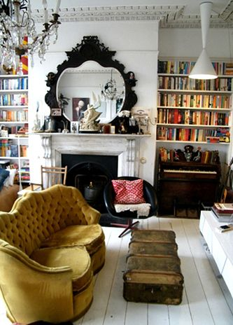 Painted white floors, mustard couch and books for days. Boho living room.