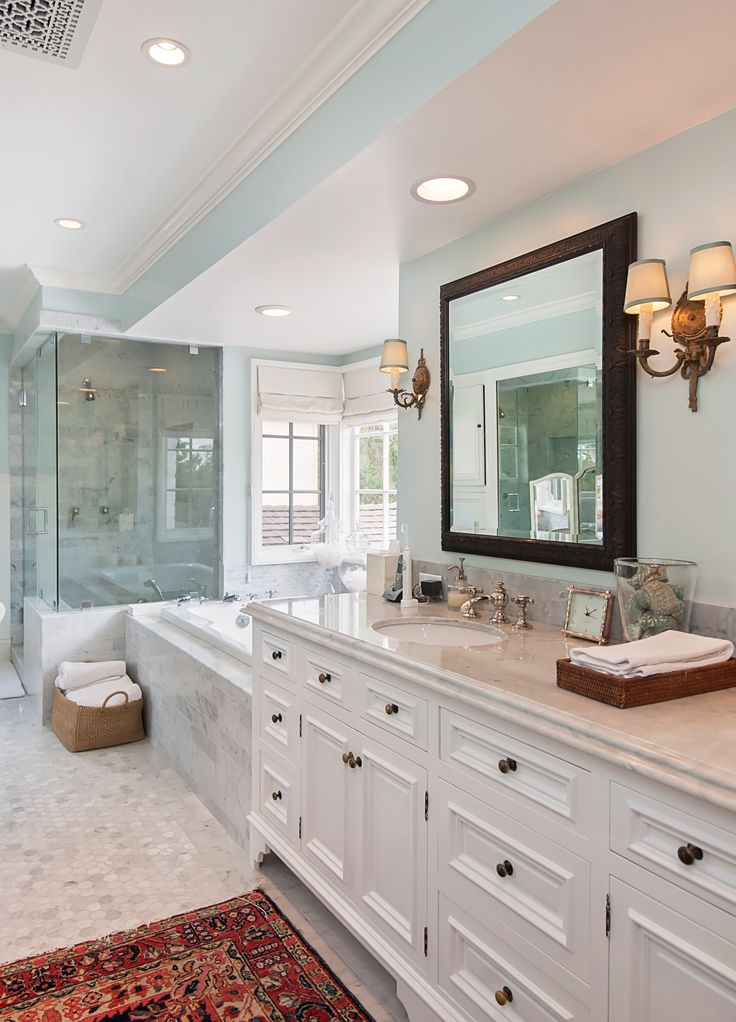 Master bathroom with mirrored vanity, pale blue walls, oriental rug, marble subway tile, French bay windows and a giant bathtub with jets and jacuzzi and candles | Los Angeles Home | L.A. Luxury House in Bel Air | Katy Lee Estate Sales | www.klestatesales.com
