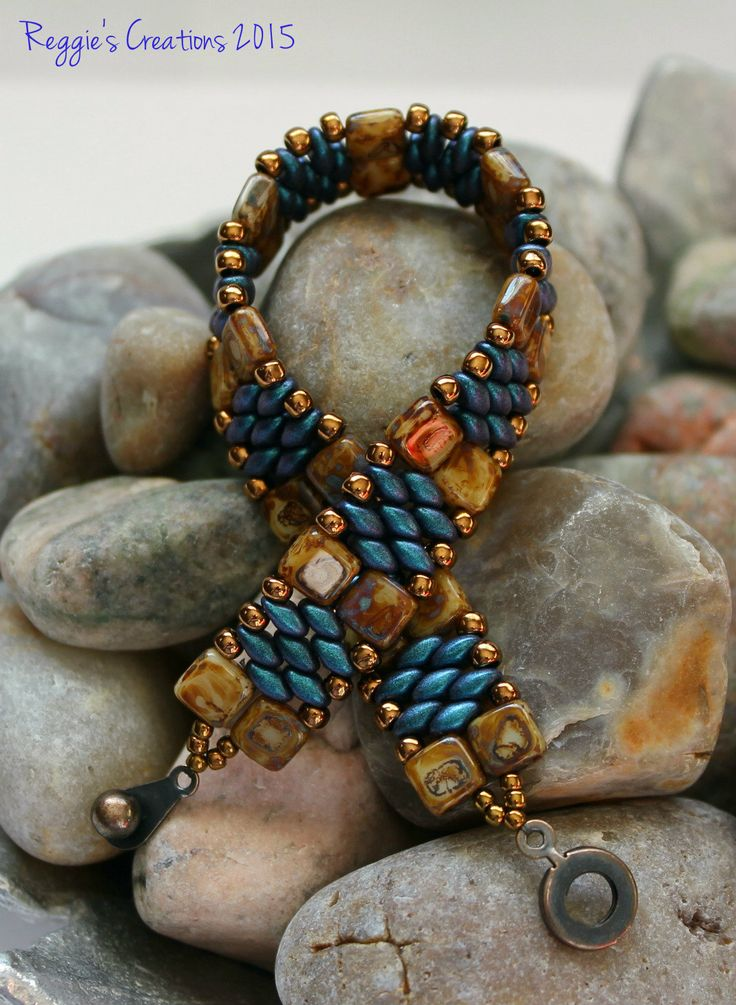 Probably one of my favorite color combos yet.  Love love love these Indigo Orchid Superduo Beads.  Here they are combined with Light Beige Picasso Czechmate Tile Beads embellished with Metallic Matte Bronze Toho Seed Beads.