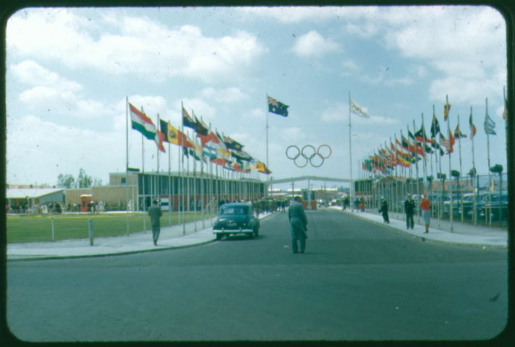 The entrance to the Olympic Village in Heidelberg West during the 1956 Melbourne Olympic Games. It features an anvenue of national flags, leading to the village gates surmounted by large Olympic rings.  One of a set of 147 35mm Kodachrome slides donated to the Museum in 1987. The images are all taken during the Olympic Games held in Melbourne in November and December, 1956.