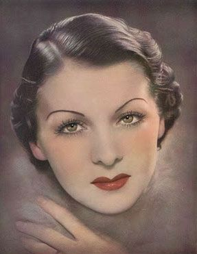 Gabriela Hernandez highlights the Six Top Make-up Tips for achieving the 1930s face.        Eyebrows are plucked very thin and drawn high on the face.        Curled lashes are darkened with mascara for long, sharp lashes.        Eyes are outlined with a brown grease pencil        Powder, cream paste, or liquid rouge highlights the cheeks.        Powder in ivory with a pink tone is used as foundation        Lips are full with two long mounds that flare at the corners.