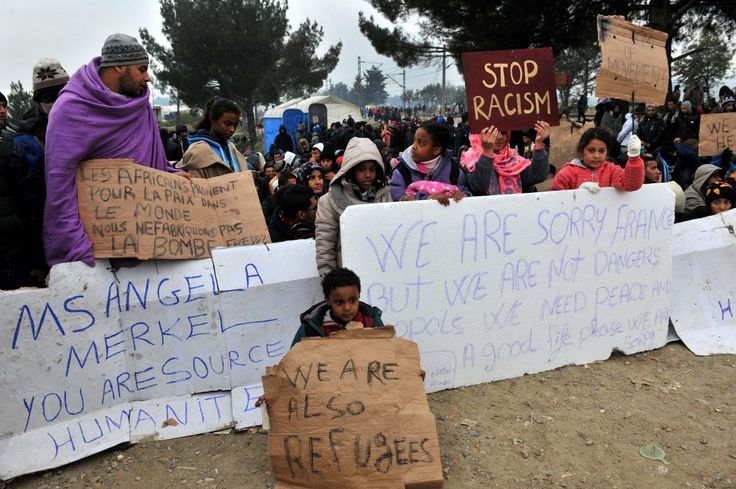 Migrants and refugees hold a placard (C) reading 'We are sorry France' refering to the Paris attacks as they wait to cross the border between Greece and Macedonia near the Greek village of Idomeni on November 21, 2015. Serbia and Macedonia, which lie on the main migrant route to northern Europe, have begun restricting the entry of refugees to just those from certain countries, the UN refugee agency said on November 19. AFP PHOTO /SAKIS MITROLIDIS (Photo credit should read SAKIS…