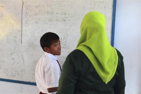 Endiansyah Mohammad (L) talks to his teacher during class in Dompu, Indonesia, November 20, 2012.  REUTERS/Beawiharta