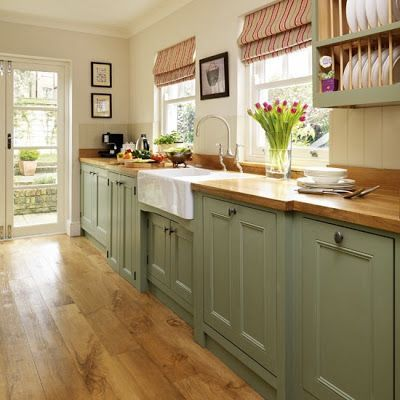 Sage green lower cabinets, leave uppers in honey stained knotty pine. Dark wood floors and butcher block countertops in the honey stain. Cream colored beadboard backsplash. Red and yellow accents.