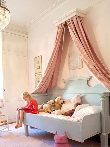 A bed canopy is an especially nice touch in a little girls bedroom. Here's a good example of how you can use simple curtain panels (extra long) and a cornice (hung near the ceiling) to create a fun and flowing canopy to frame your child's bed.