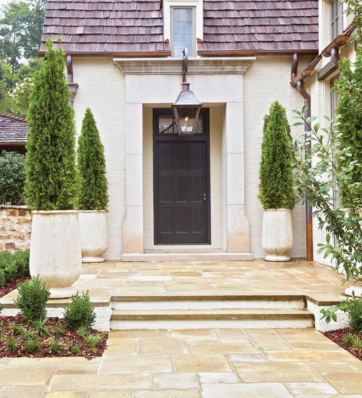 A mistura certa. O exterior da casa tem uma grande variedade de texturas, como um telhado de cedro, tijolos pintados, bordadura de  calcário e pavimento de concreto. A paleta neutra mostra a porta de mogno pintada na cor de ébano.  Fotografia: Jean Allsopp.