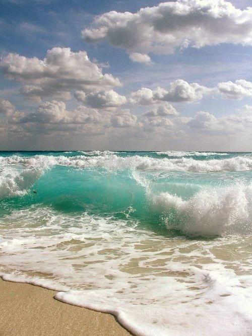 Aqua waves and puffy white clouds