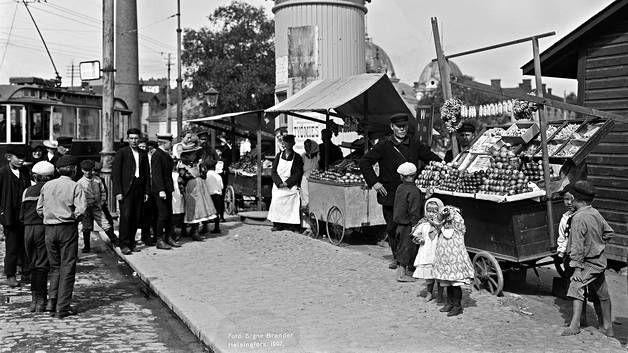Venäläisiä hedelmäkauppiaita Hakaniementorilla vuonna 1907. *** Valokuvien vanha Helsinki on samalla outo ja tuttu. Kaupunkikuvaaja Signe Brander tallensi teollistuvan kaupungin maisemaa jälkipolville ja Ilta-Sanomien kuvaaja Pete Aarre-Ahtio kävi kuvaamassa samoja paikkoja yli sata vuotta myöhemmin.