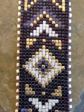 Hand-loomed in four shades of cube beads, this bracelet features a background in a deep purple called gunmail amethyst. Geometric accents are woven in transparent tanzanite, cream, and gold. It fastens with a bronze toggle clasp. LENGTH: 7.5 inches WIDTH: 1.25 inches See it in