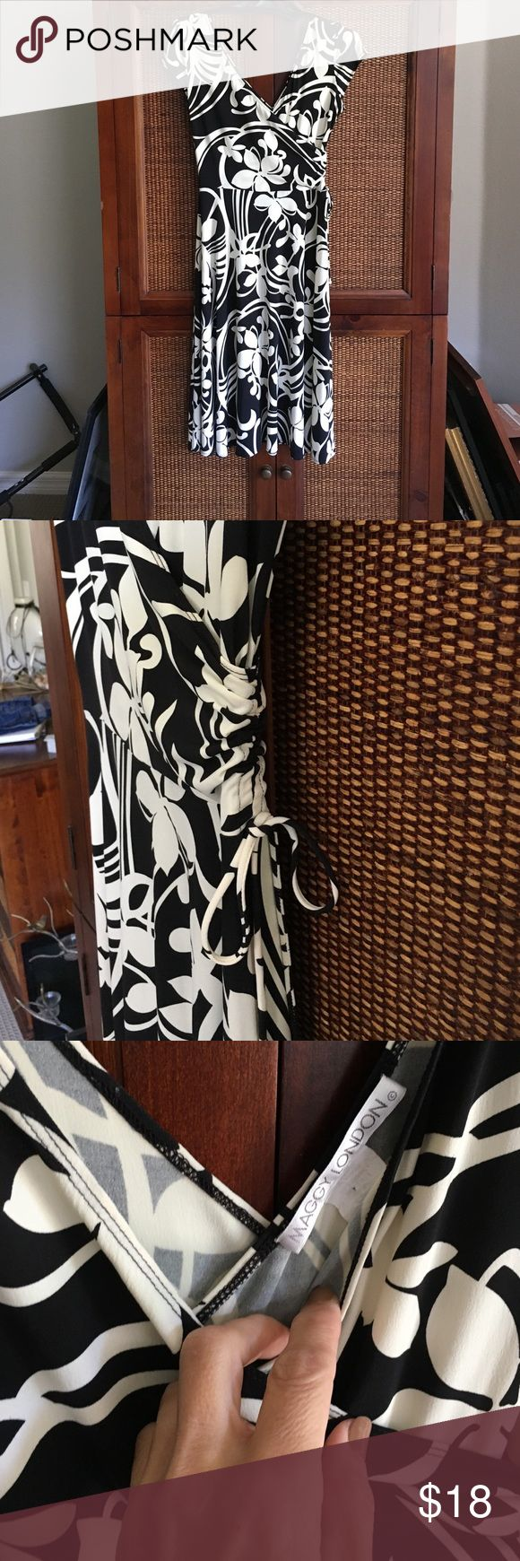 Black cream floral print sexy midi length dress 12 By Maggy London. Super cute style low cut in front and back with a cross cross styling. Full skirt bottom. Sz 12. Cute side ruching with tie accent. Like new and smoke free home. Perfect for a summer wedding or party. MIDI length. Maggy London Dresses Midi