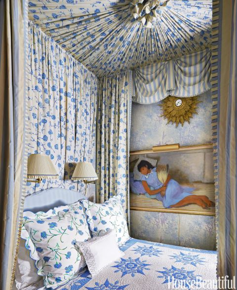 Florals and united by the colors of blue and white create a restful air. The painting is by an aunt, Lily Cushing.  Sconces, Hansen Lighting.