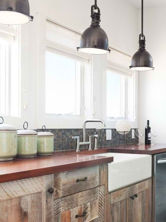 with red exposed brick, redish worktops, apron sink and wood cabinets below -- like the lights too!