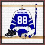 A personalized ice hockey jersey in blue and white hanging in a sports locker room with a helmet, ice skates and an ice hockey stick. The jersey can be fully customized with the number and name of your choice to make a great gift for the ice hockey fan, ice hockey player or ice hockey coach.    Other colours available in our store and we welcome custom requests for different colour combinations for your team colours. Contact us via our store with your request prior to purchase and we will be…
