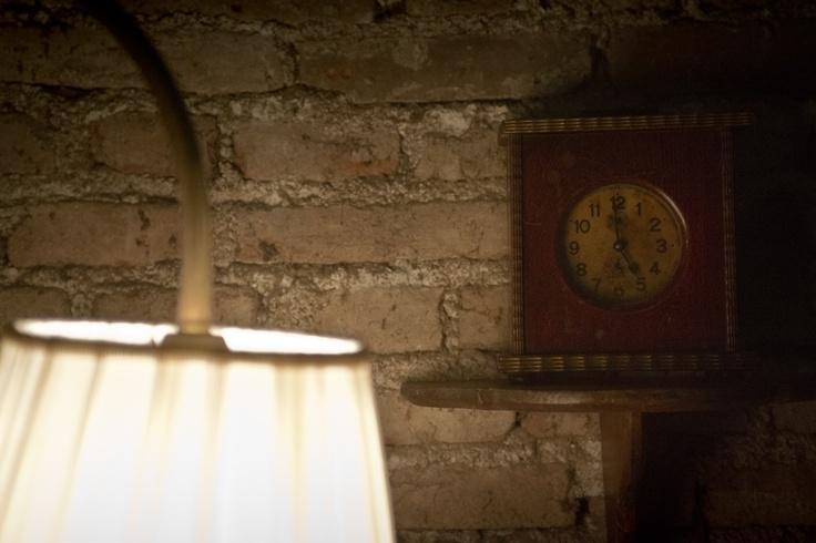 Orologio di antiquariato e lampada vintage per angolo suggestivo nell'allestimento della sfilata Niu' AW2013/14
