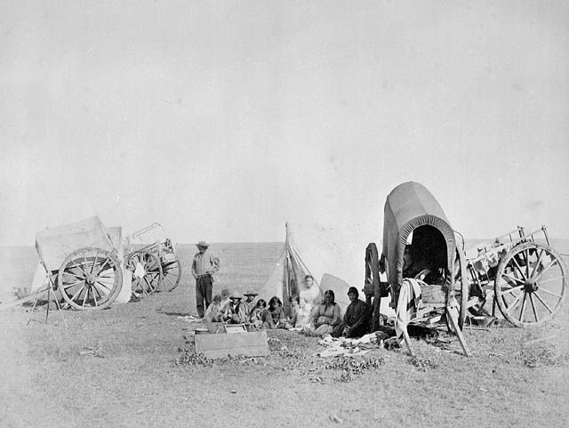 Camp scene of Métis people with carts on prairie. 1874