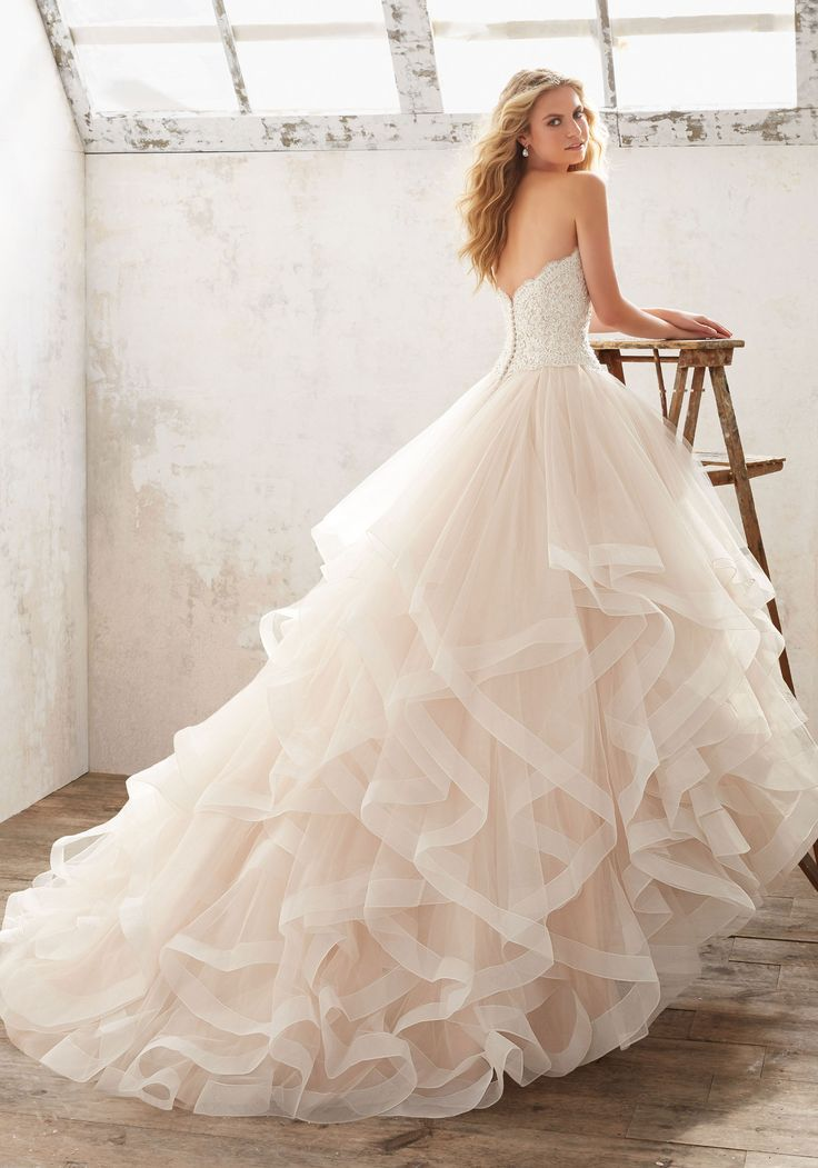Soft and Ethereal, This Ruffled Bridal Ballgown Features a Crystal Beaded Alen?çon Lace Bodice, and Horsehair Trimmed Flounced Tulle Skirt. Covered Button Detail Along Back. Colors Available: White, I
