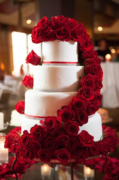 How elegant are fresh red roses ascending a four-tiered, white wedding cake?