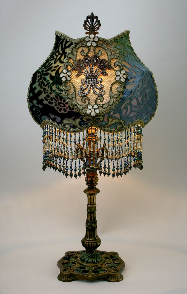 Detailed, ornate early 1900s metal lamp base holds a Cameo shade in tones of dark green midnight blue. Antique hand-dyed cut velvet, gold metallic lace and scroll trim overlay the panels and a pair of vintage rhinestone encrusted appliqués adorn the front and back. This lamp reminds me of old Hollywood glamour.