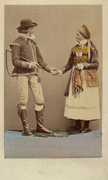 SE Herrestad. Dräktdockor med huvuden skulpterade av C. A. Söderman, visade på världsutställningen i Wien 1873. Par i dräkter från Herrestad, Skåne. Handkolorerad.