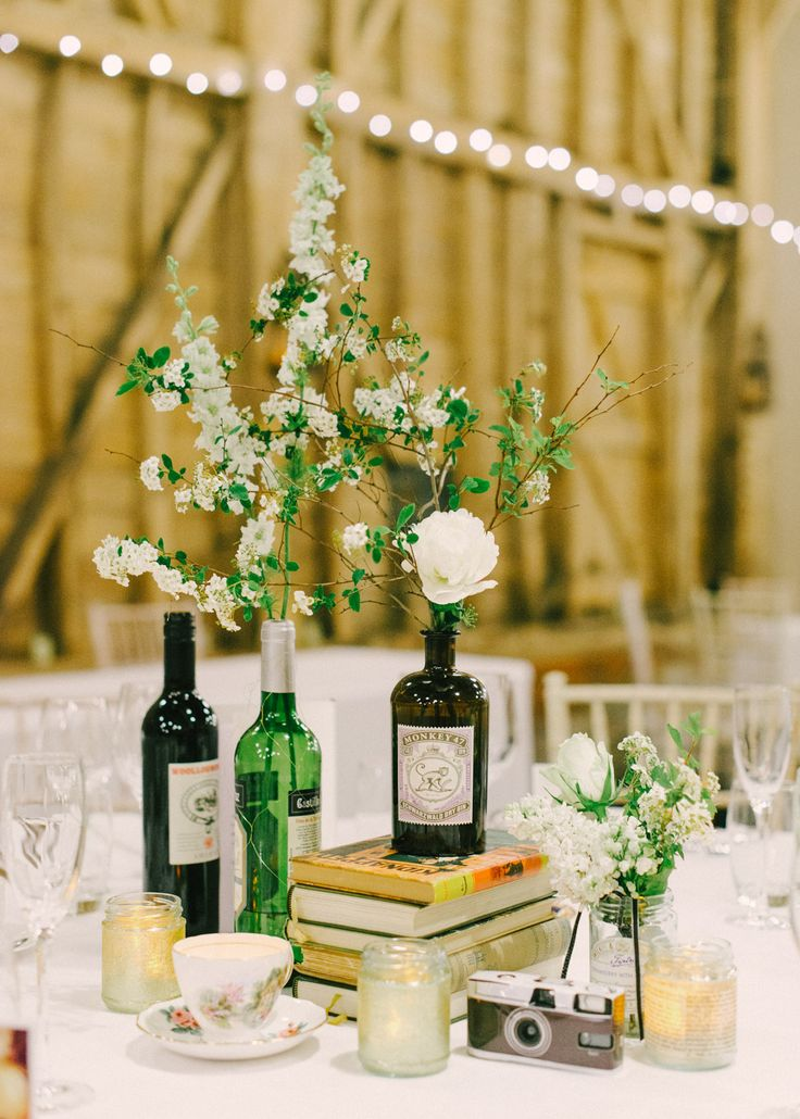 Antique Books and Gin Bottles filled with Flower Stems as Table Centrepieces | Elegant literature themed wedding at Long Barn, Childerley Hall | Images by Hannah Duffy Photography | http://www.rockmywedding.co.uk/eleanor-james/